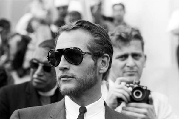 Paul Newman in a vintage photo sporting oversized aviator-style sunglasses