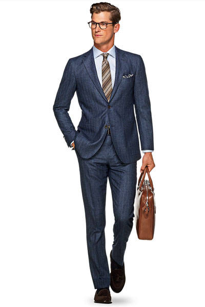 A man wearing a herringbone suit and tie