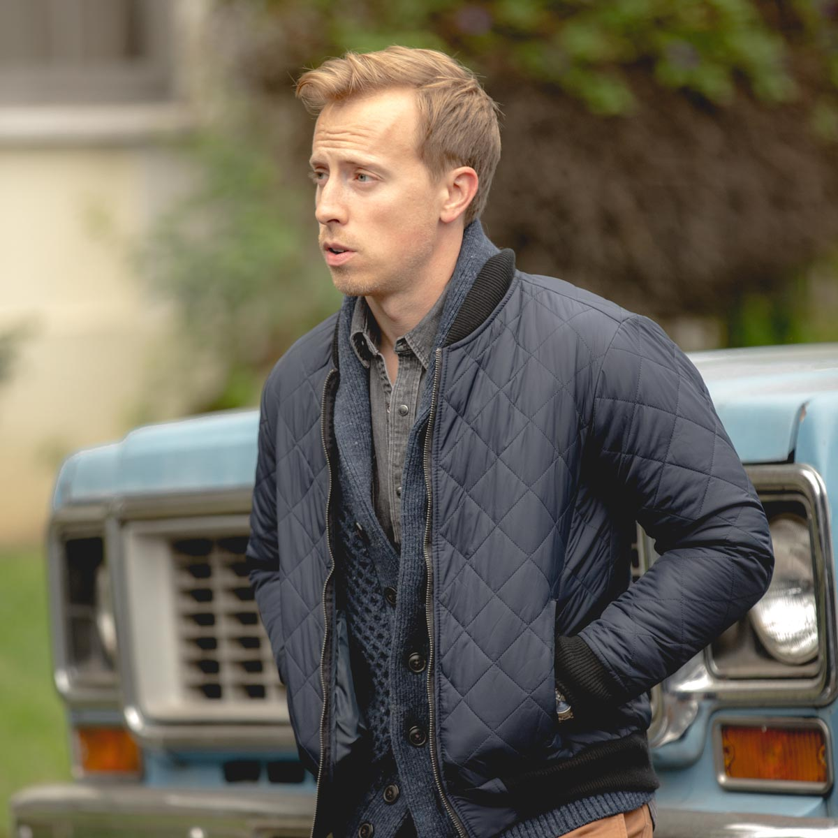 man wearing quilted bomber jacket with sweater
