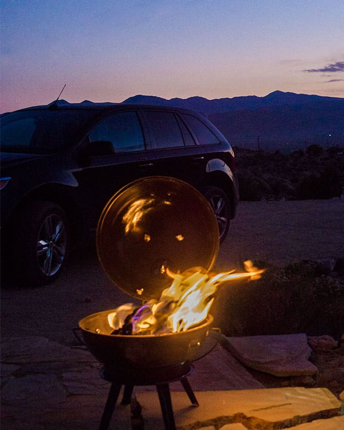 A grill in front of a sunset