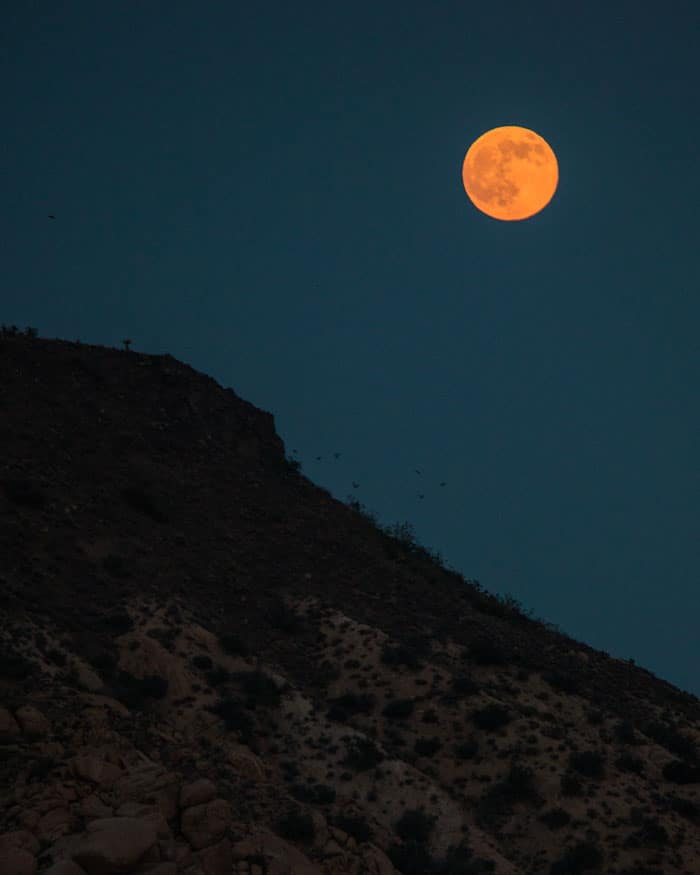 A large mountain in the dark with orange moon