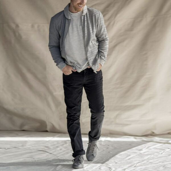man wearing black pants grey jacket and grey and white striped shirt