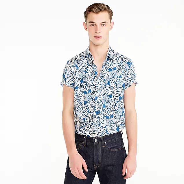 A person standing posing for the camera wearing a floral shirt