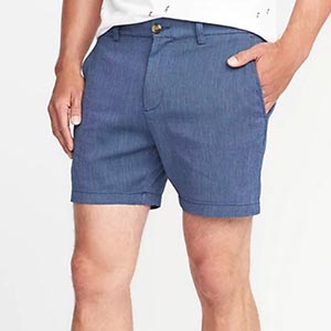 A person standing posing for the camera with blue shorts