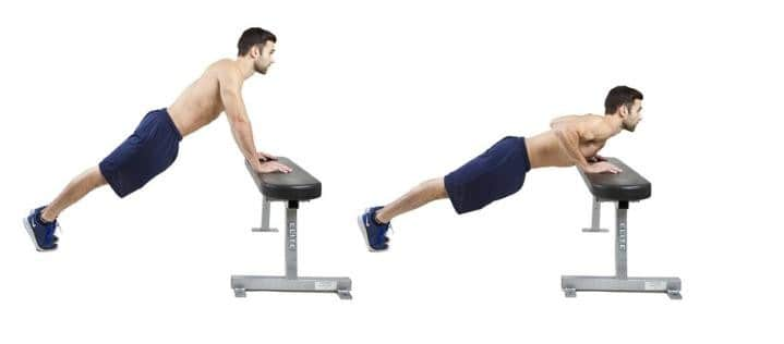 Image of man doing pushup exercises on a gym bench