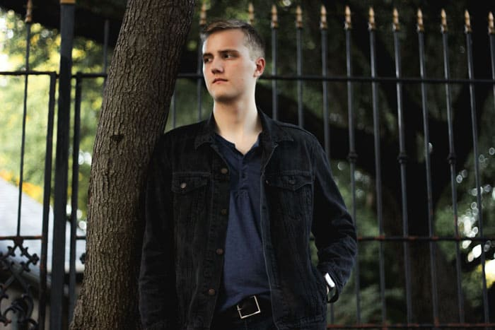 A person standing in front of a fence, with Stacy Man wearing black trucker jacket with blue henley