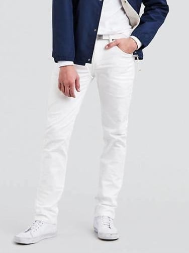 A person standing posing for the camera wearing white stretch jeans