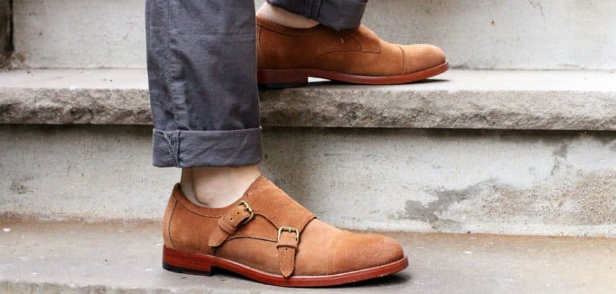A pair of feet standing on a sidewalk wearing monk strap shoes