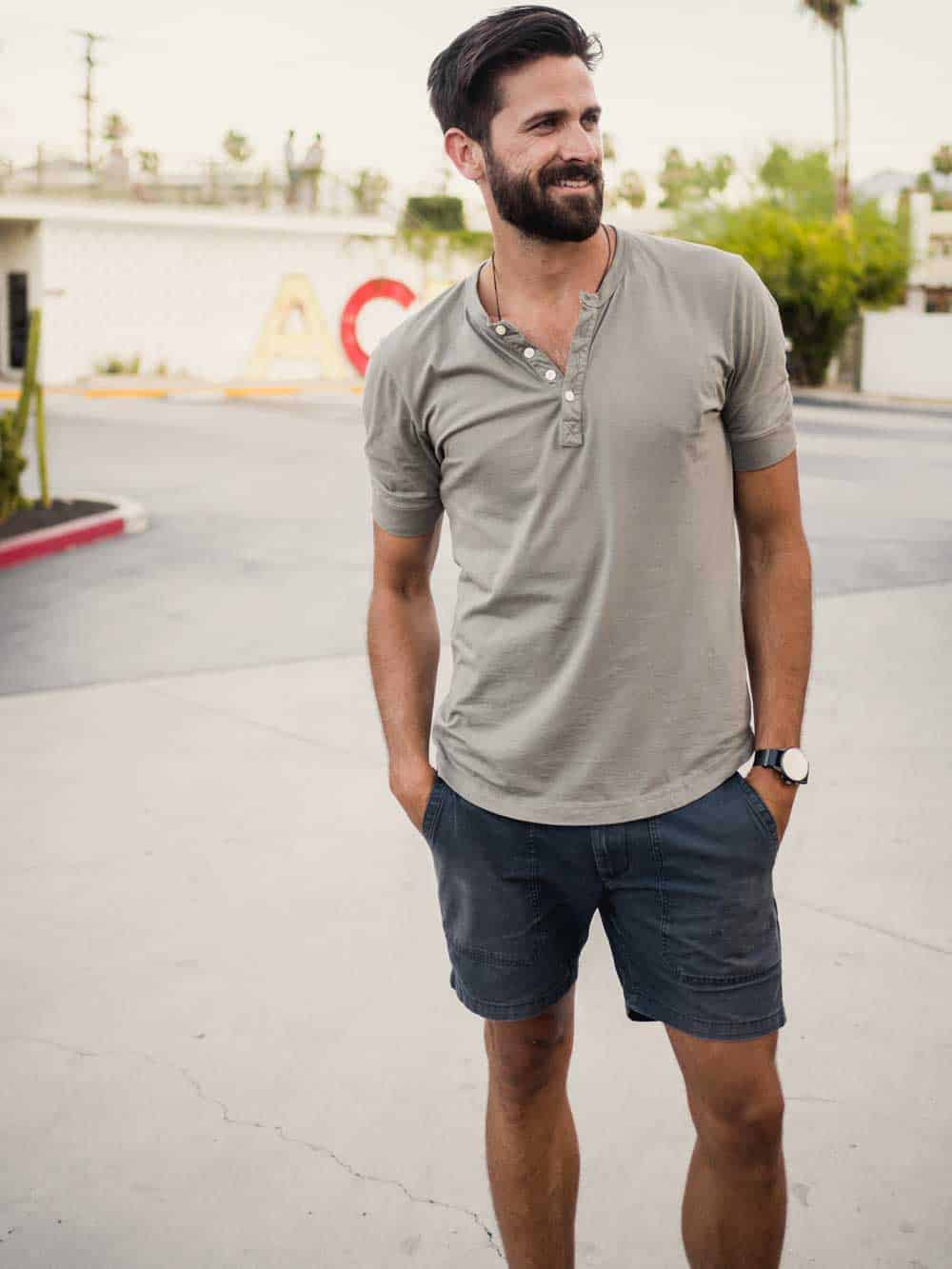 A man standing in a parking lot with a short sleeve henley