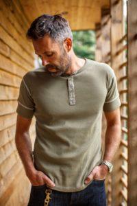 man wearing green short sleeve henley style shirt