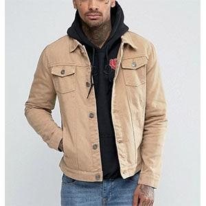 A man standing in front of a coat weraing a khaki trucker jacket