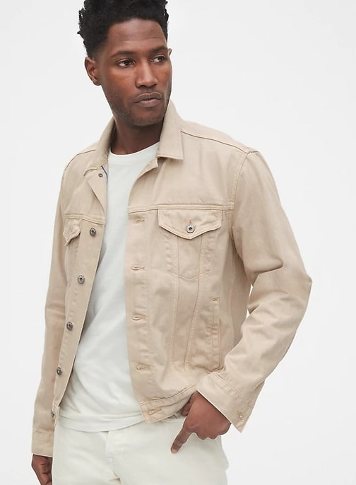 A person standing posing for the camera weraing a cream colored trucker jacket