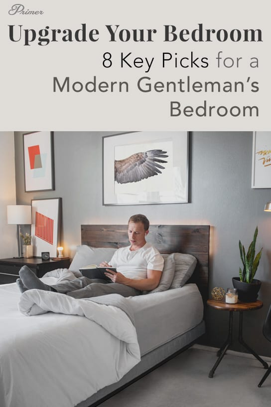 A person sitting on a bed in a gray bedroom