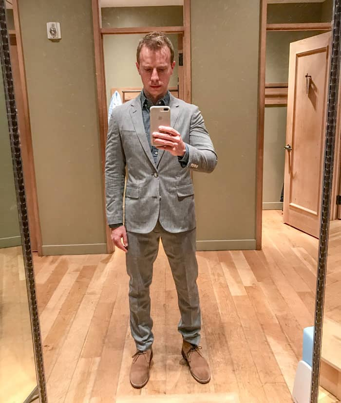 man trying on suit in fitting room