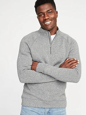 A person standing posing for the camera wearing a gray sweater