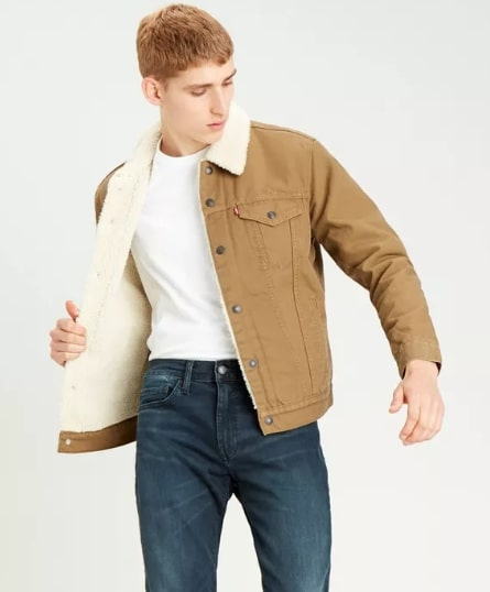 A person standing posing for the camera wearing a tan trucker jacket