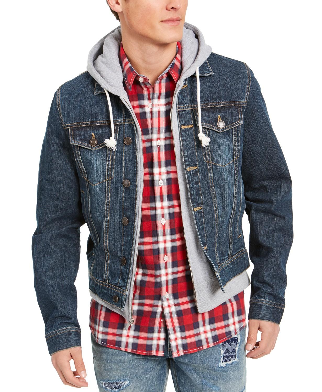 A man wearing a denim jacket over a hoodie