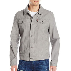 A person standing posing for the camera wearing a gray trucker jacket