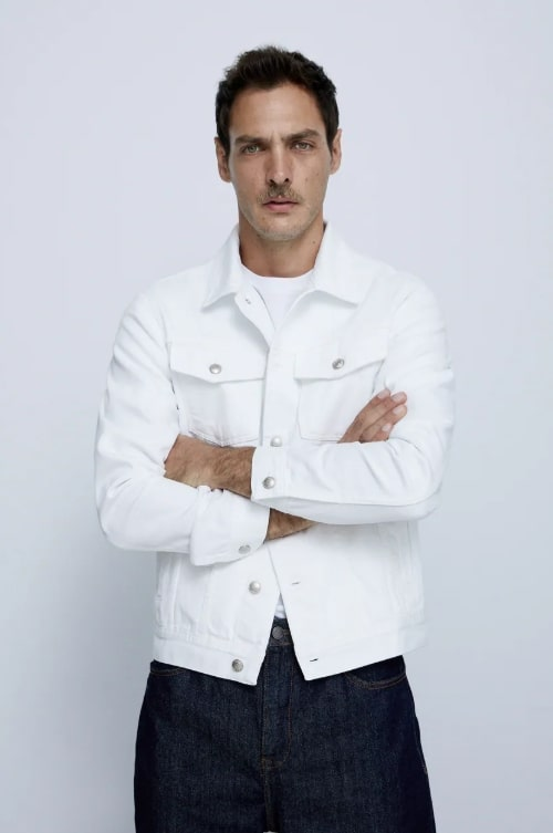 A person standing posing for the camera wearing a white denim trucker jacket