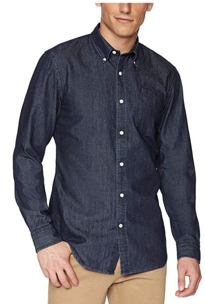 A person standing posing for the camera wearing a denim shirt