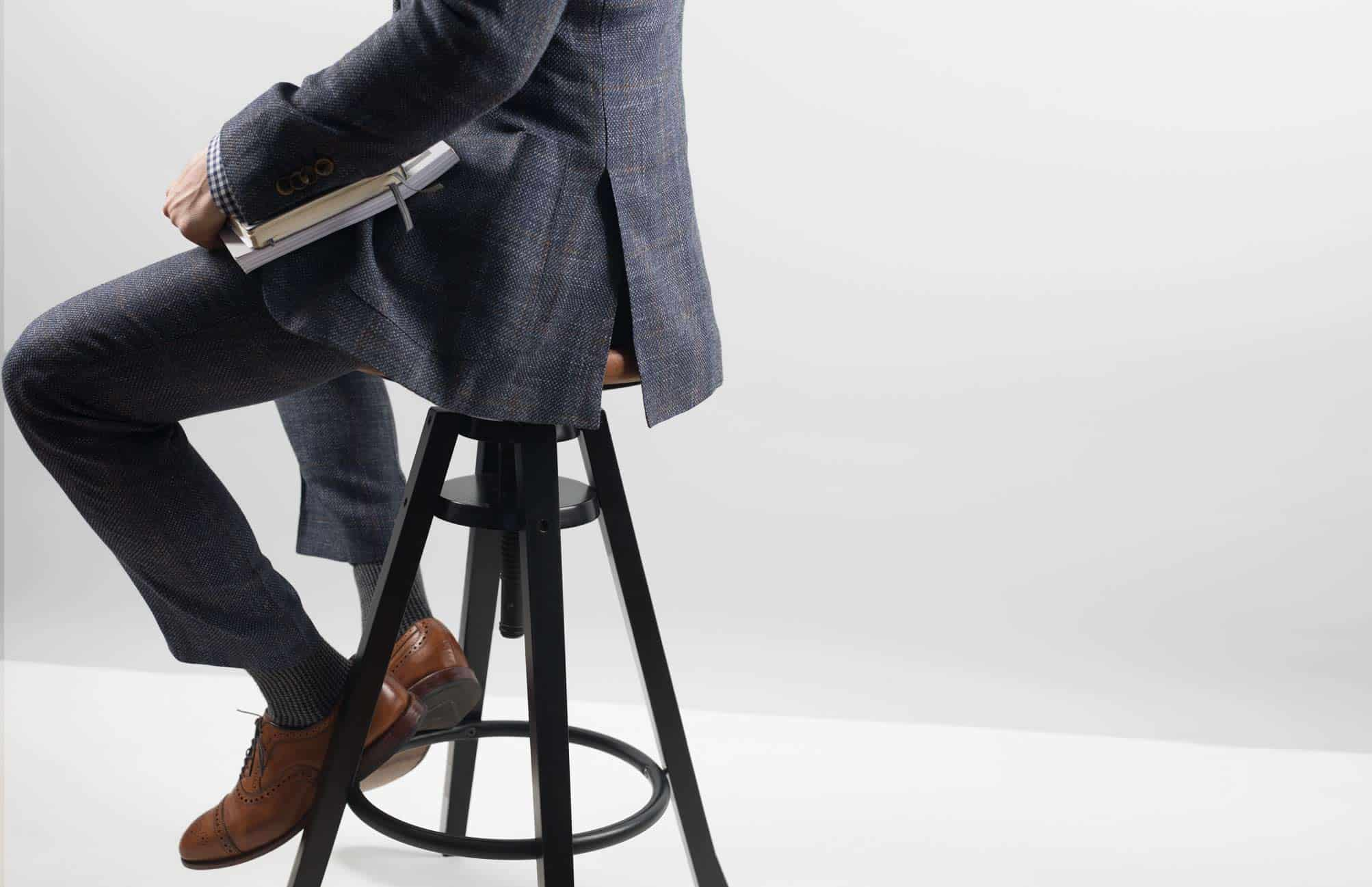 A person wearing a suit sitting on a stool
