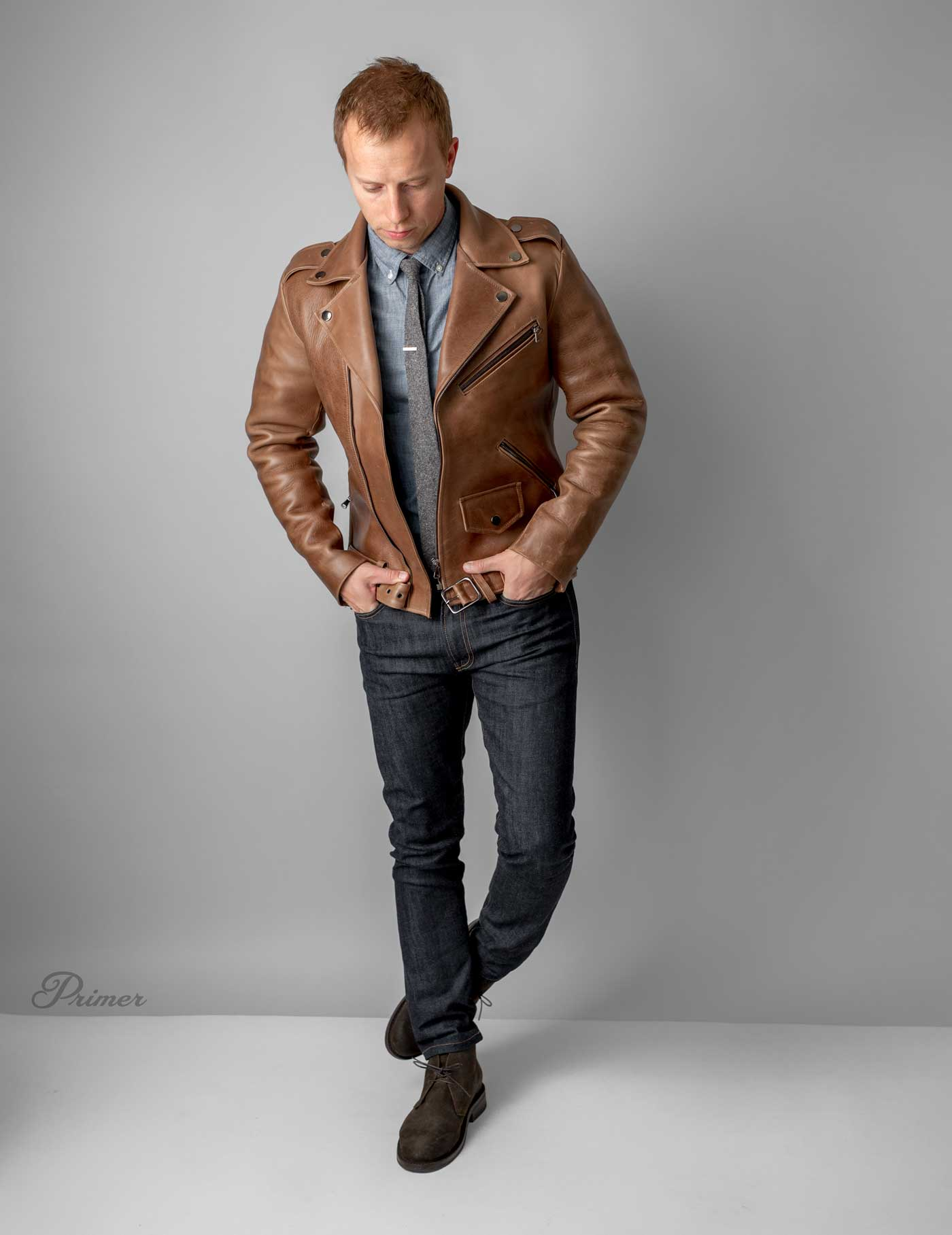 brown leather motorcyle jacket with jeans and tie