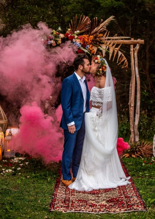 A groom and bride kissing with pink smoke