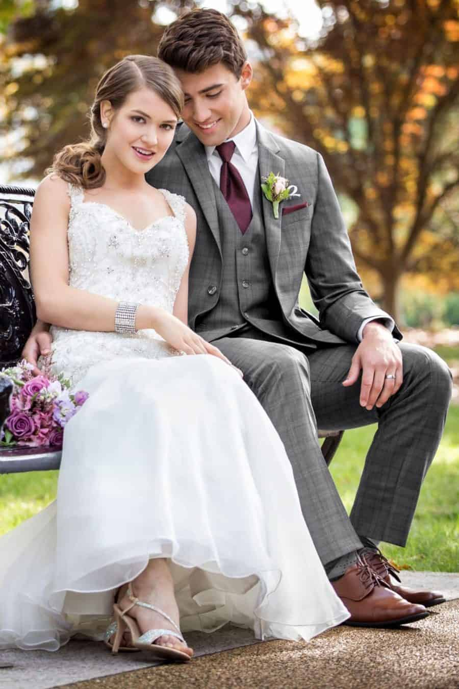 A wedding couple that are sitting on a bench
