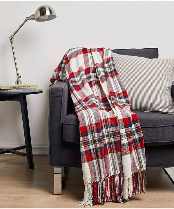 A bedroom with a blanket and a chair