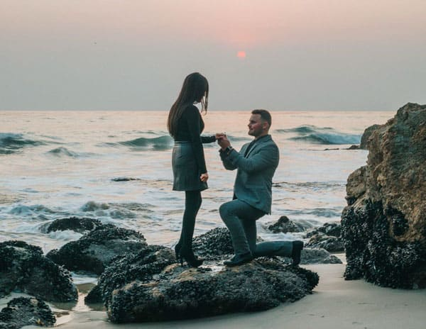 man proposing on the beach engaged