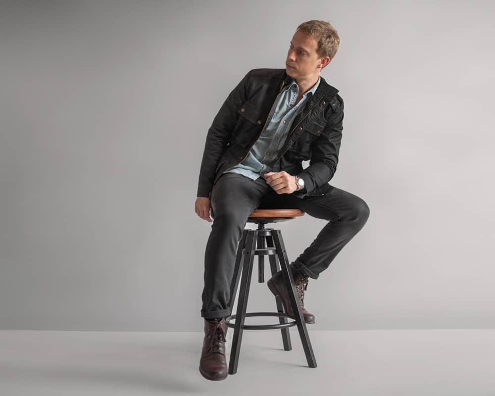 A man wearing a denim shirt and gray pants