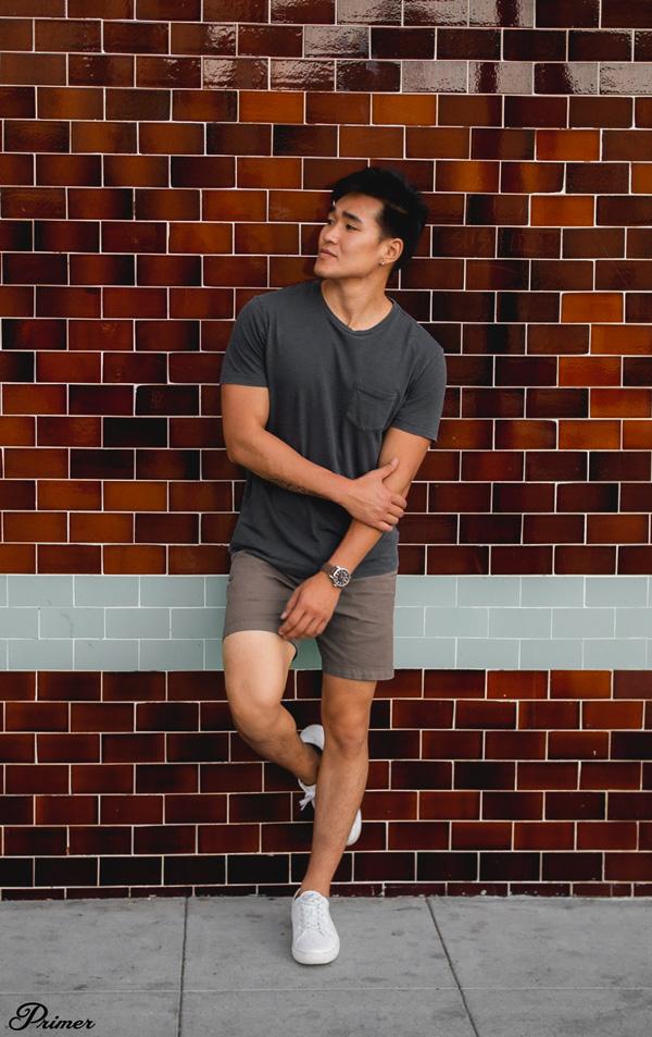 A man standing next to a brick wall