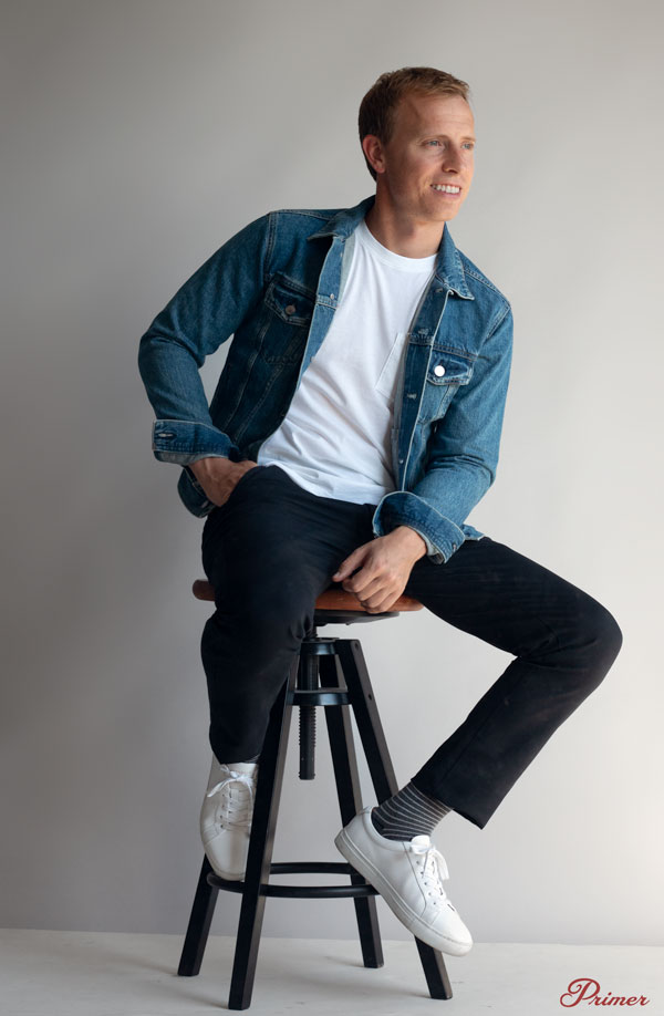 man wearing light denim jacket, white t-shirt, blue chinos and white sneakers sitting on a stool