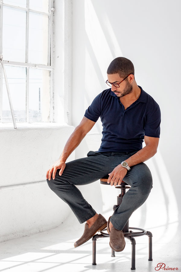 a man in glasses wearing a short sleeve henley and gray pants on a stool