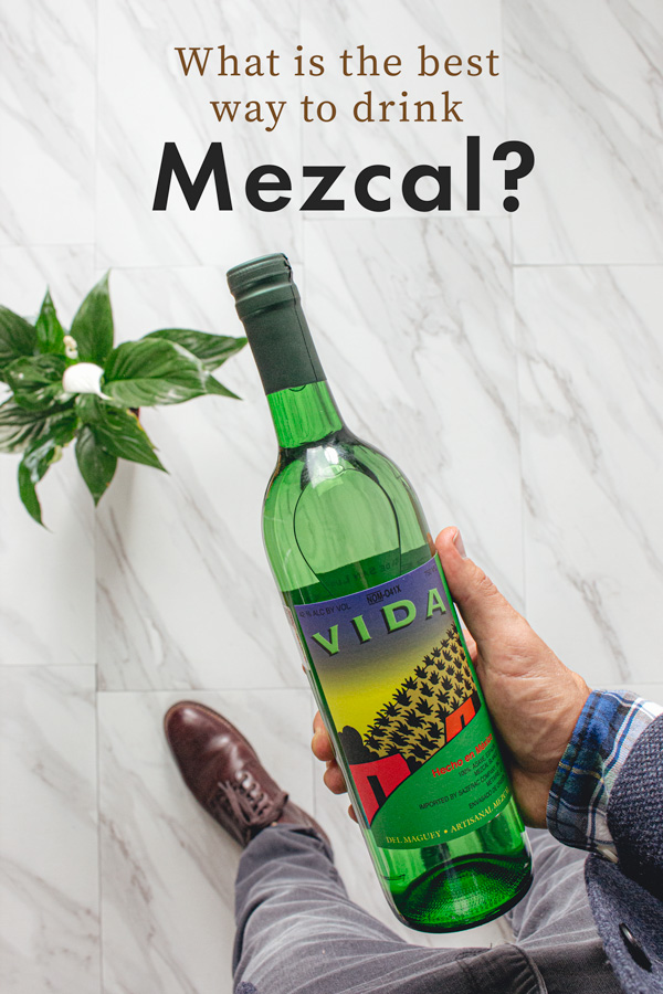 A person holding a bottle of mezcal