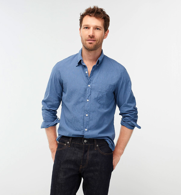 A person standing posing for the camera in a blue shirt