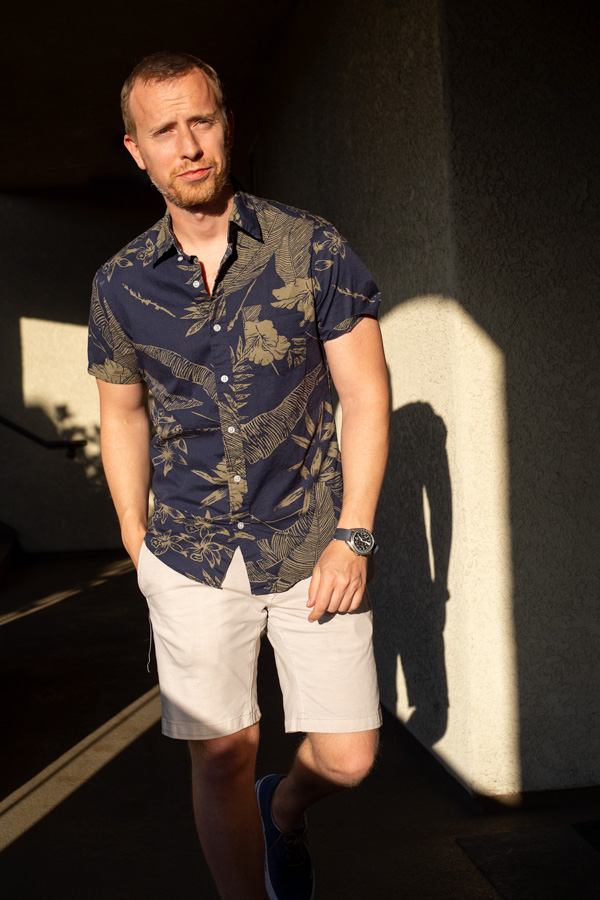 A person standing posing for the camera with a floral short sleeve shirt