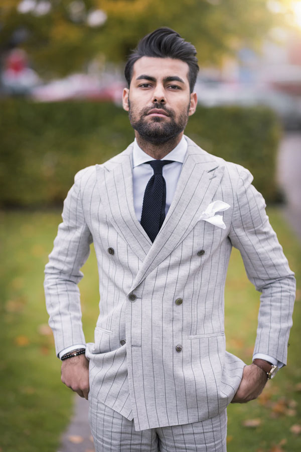 man in suit wearing cutaway collar shirt