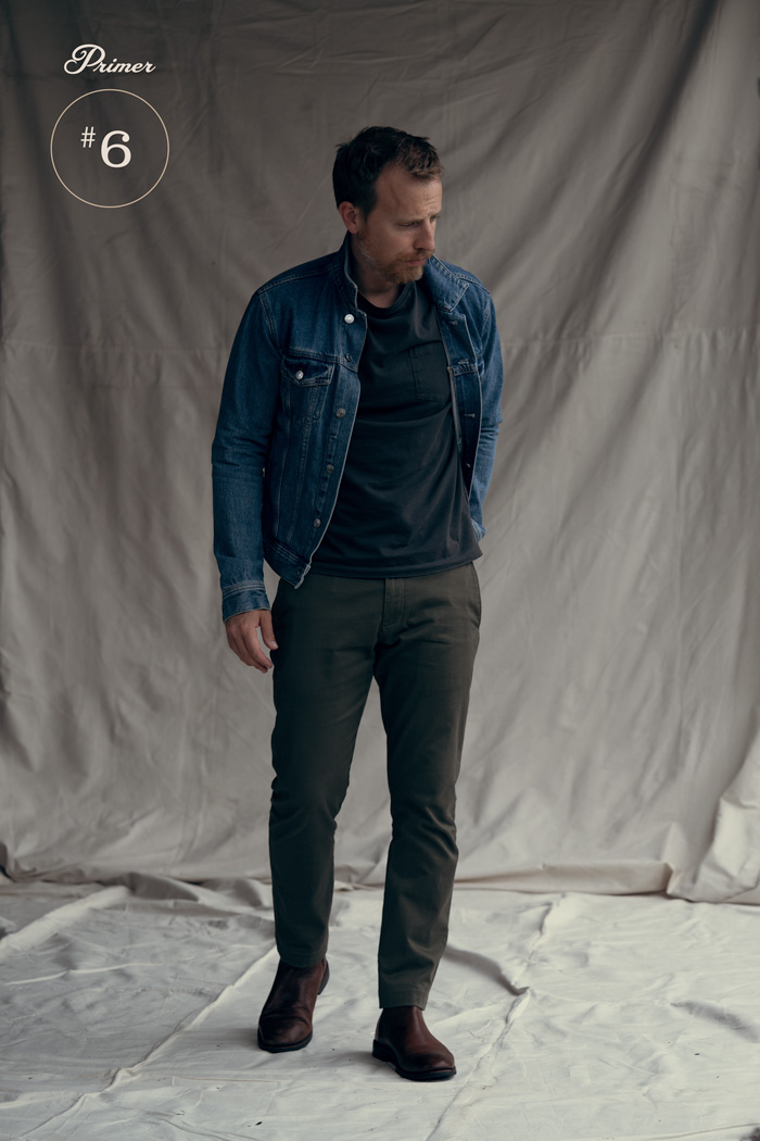 Men's outfit example with denim jacket, black t-shirt, green chinos, and chelsea boots