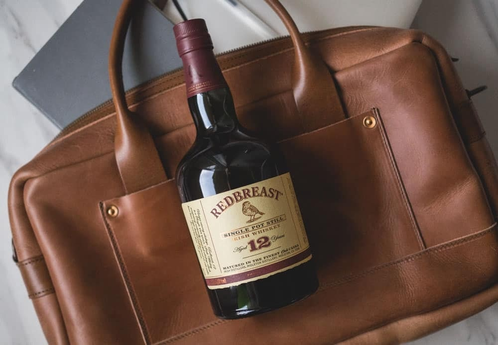 Image of a bottle of whiskey on a leather briefcase