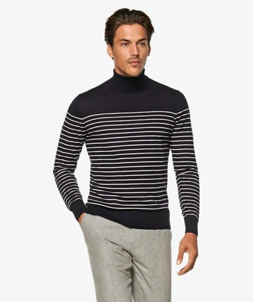 A man wearing a navy and white striped turtleneck top