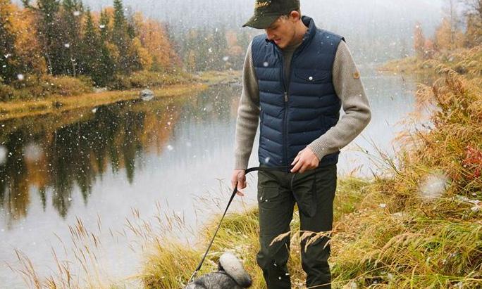 man wearing fjallraven vest walking next to water