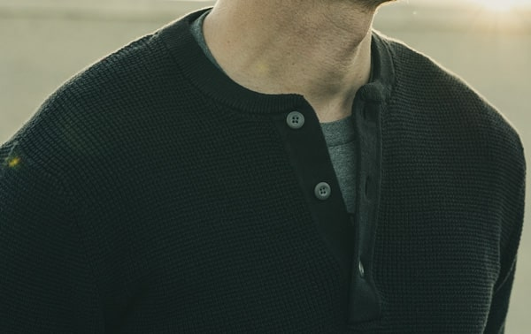 close up of the collar line of a black henley style shirt for primer magazine