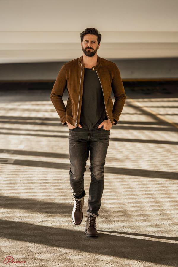 man wearing brown racer jacket with tshirt walking in garage