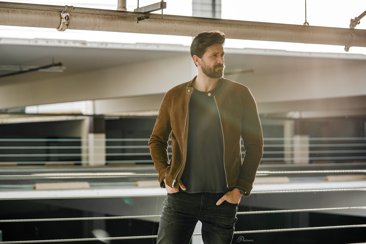 man wearing brown leather racer jacket with gray tshirt and jeans