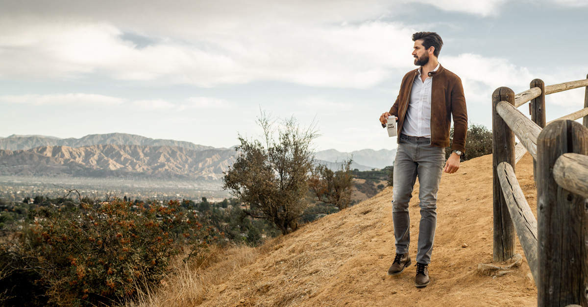 man wearing leather racer jacket in front of landscape