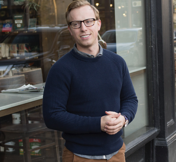 man wearing a dark blue rib stitch style sweater and glasses for primer magazine