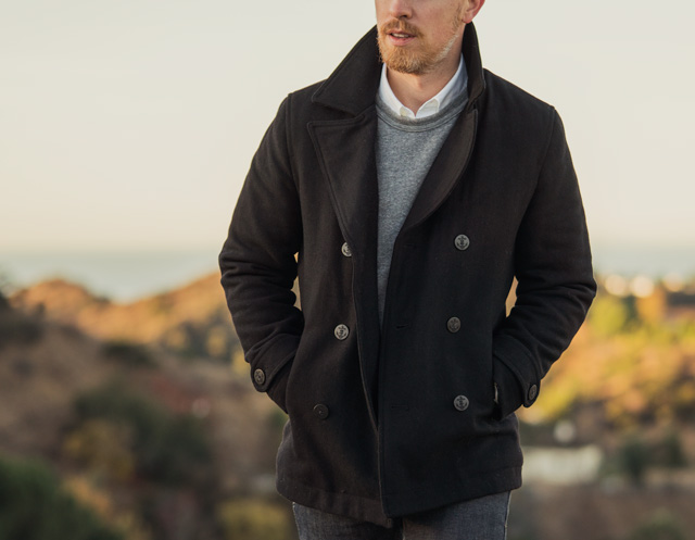 Man wearing black pea coat with gray sweatshirt and white oxford cloth button down