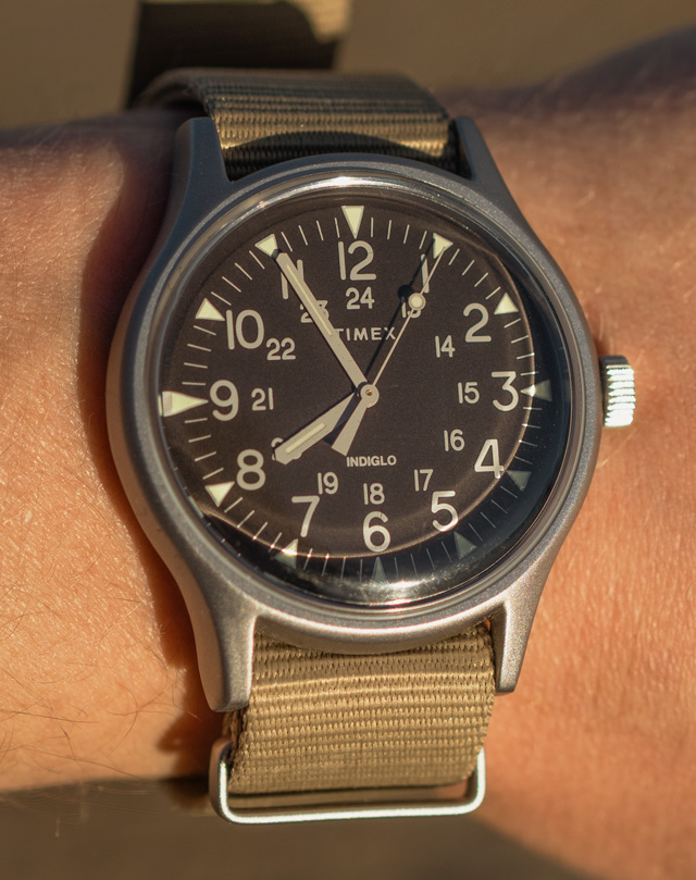 Timex watch with a black face and tan cloth NATO strap
