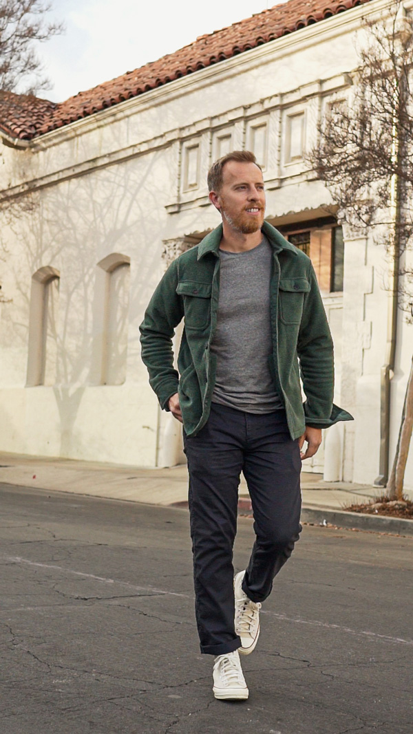 roupa casual masculina ideia camisa verde jaqueta camiseta cinza e chinos azuis com tênis Converse